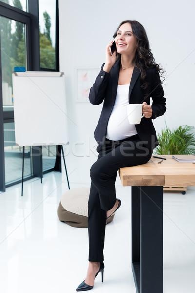 pregnant businesswoman talking by phone Stock photo © LightFieldStudios