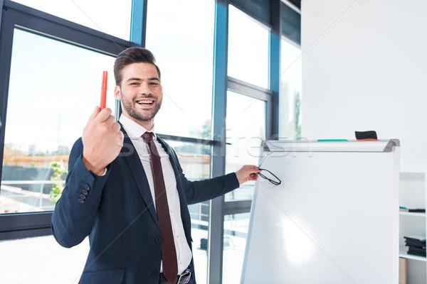smiling businessman with whiteboard Stock photo © LightFieldStudios