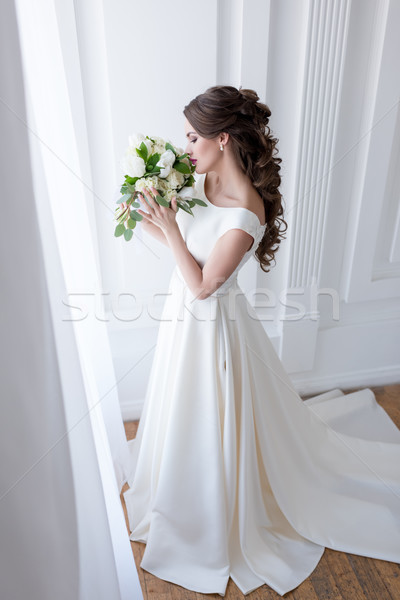 elegant bride in traditional white dress sniffing wedding bouquet Stock photo © LightFieldStudios
