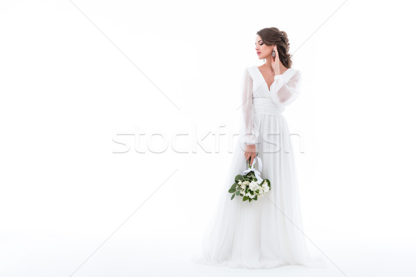 bride posing in elegant white dress with wedding bouquet, isolated on white Stock photo © LightFieldStudios