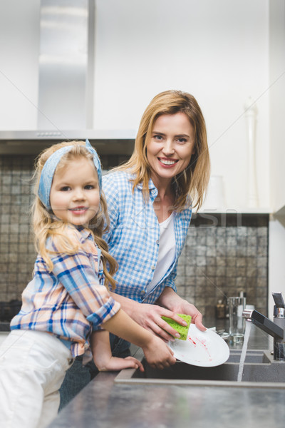 little daughter and mother looking at camera while washing dishes after dinner together at home Stock photo © LightFieldStudios