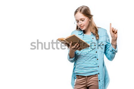 beautiful teenage girl in eyeglasses reading book and pointing up with finger isolated on white Stock photo © LightFieldStudios