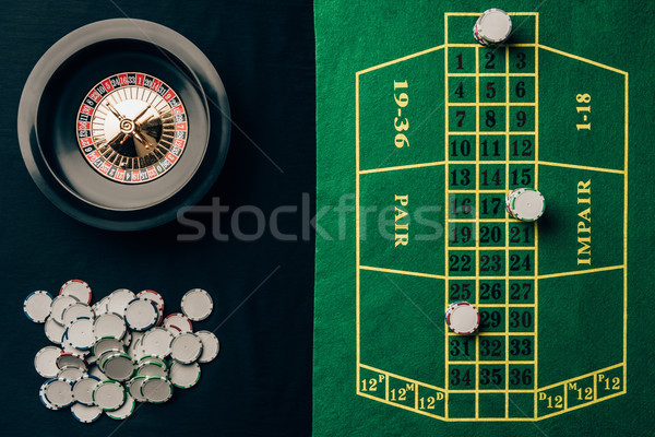 Casino table with roulette and round chips Stock photo © LightFieldStudios