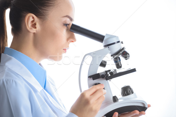 side view of concentrated woman scientist looking through microscope on white Stock photo © LightFieldStudios