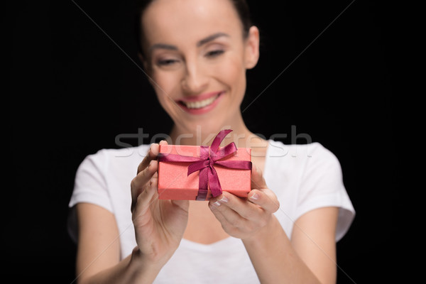 portrait of smiling woman showing gift on black, focus on foreground, international womens day conce Stock photo © LightFieldStudios