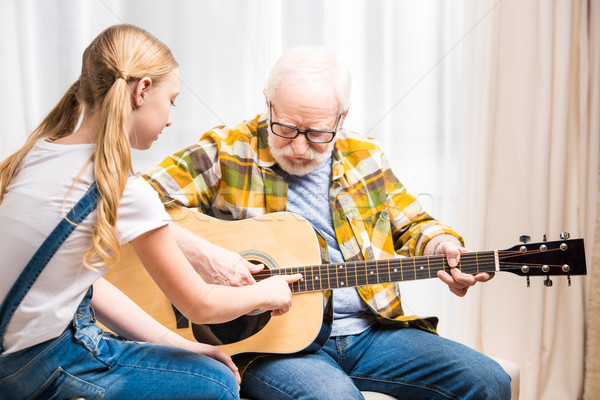 Senior man in eyeglasses teaching cute little granddaughter playing acoustic guitar Stock photo © LightFieldStudios