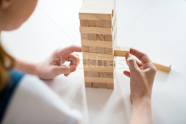 Close-up partial view of girl playing jenga game on white table Stock photo © LightFieldStudios