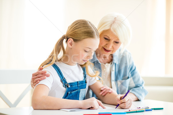 Smiling senior woman and preteen girl drawing together at table Stock photo © LightFieldStudios