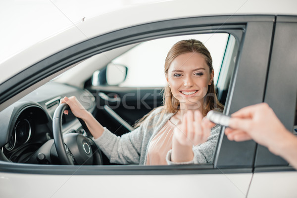 Stock photo: Person giving car key to woman sitting in car in dealership salon
