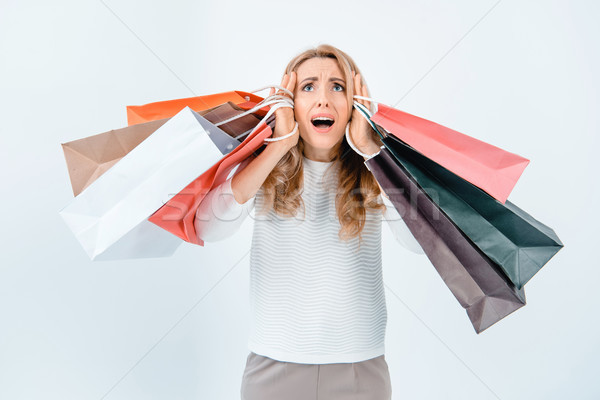 Scared middle aged woman holding shopping bags and looking up on grey Stock photo © LightFieldStudios