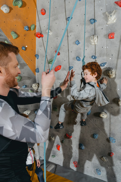 Boy on climbing wall high-fiving father Stock photo © LightFieldStudios