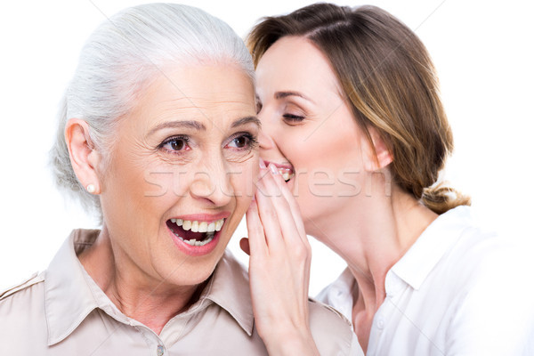 daughter whispering to senior mother Stock photo © LightFieldStudios