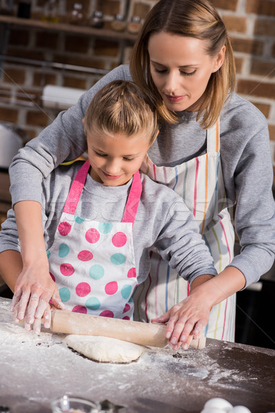 Stock photo: mother helping daughter with cooking