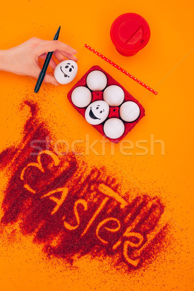 cropped image of woman holding easter egg with smiley on orange Stock photo © LightFieldStudios