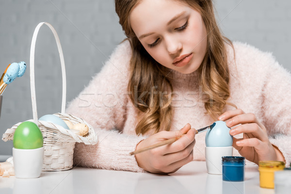 beautiful focused teenage girl painting egg for easter Stock photo © LightFieldStudios