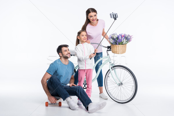 happy family with skateboard and bicycle making selfie on white  Stock photo © LightFieldStudios