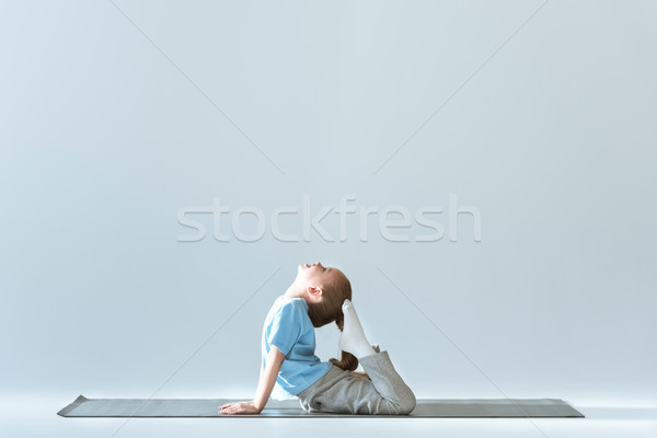 Side view of sporty girl practicing King Pigeon Posture on mat on grey Stock photo © LightFieldStudios