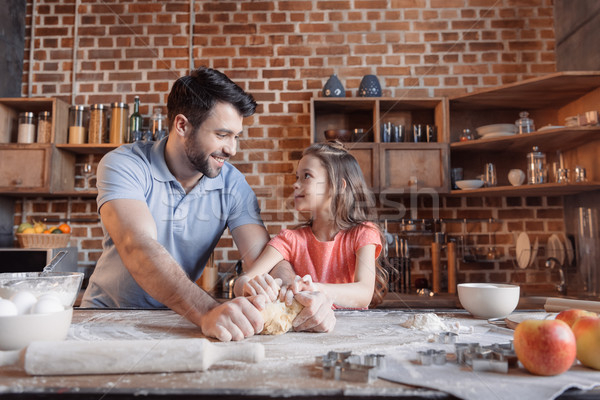'Happy father and daughter kneading dough and looking at each other Stock photo © LightFieldStudios