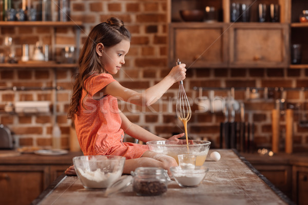 'side view of girl sitting on table and mixing ingredients for cake Stock photo © LightFieldStudios