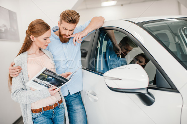 pensive couple holding catalog and choosing car in dealership salon    Stock photo © LightFieldStudios