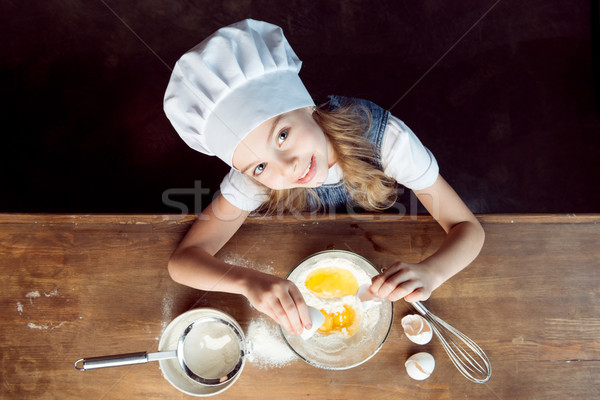 Stock photo: overhead view of girl making dough for cookies on wooden table