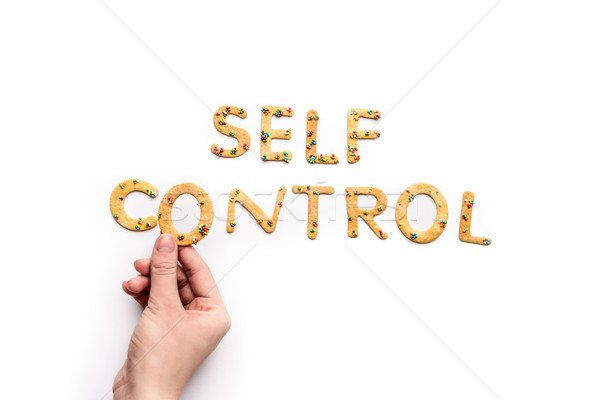 Top view of self control lettering made from sweets and hand holding letter, healthy living concept Stock photo © LightFieldStudios