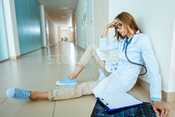 Zmęczony lekarza posiedzenia szpitala korytarz młodych Zdjęcia stock © LightFieldStudios