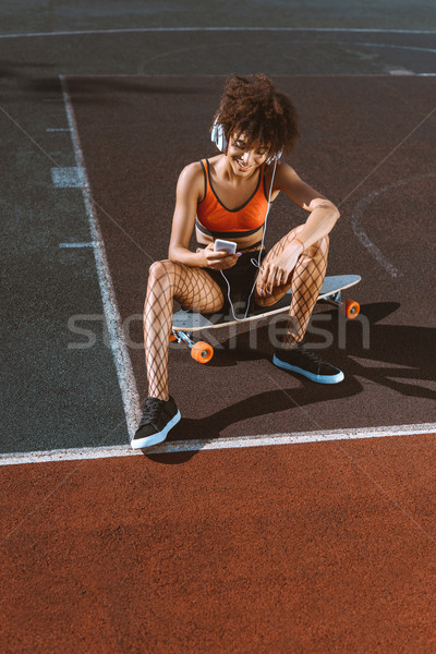 african-american woman on longboard in headphones Stock photo © LightFieldStudios