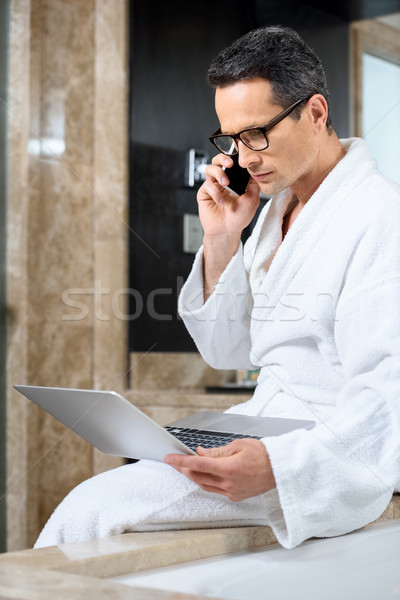 Businessman in bathrobe working with devices Stock photo © LightFieldStudios