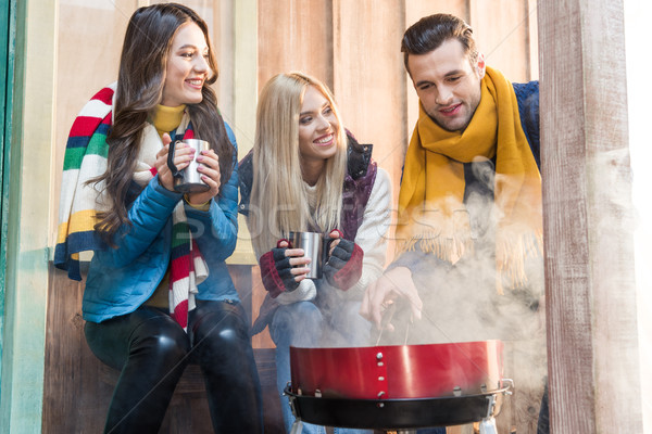 Feliz jovem amigos potável quente chá Foto stock © LightFieldStudios