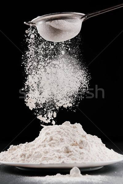 flour falling from sieve on pile isolated on black Stock photo © LightFieldStudios