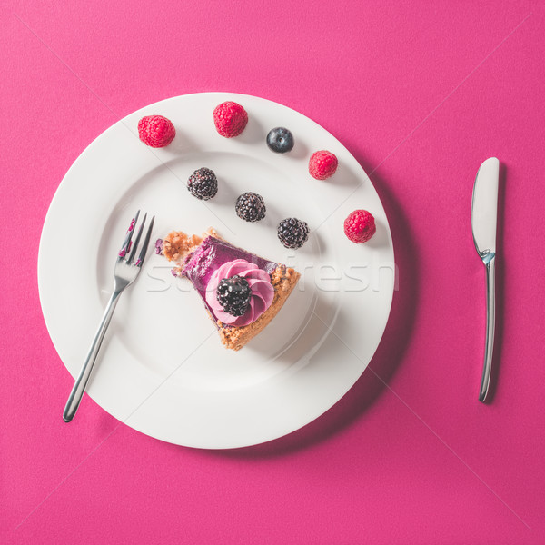 top view of bitten piece of cake with berries on plate on pink surface Stock photo © LightFieldStudios
