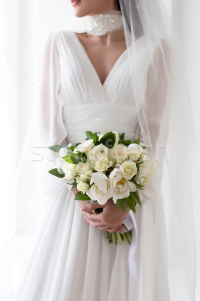 cropped view of bride in wedding dress and veil holding white bouquet Stock photo © LightFieldStudios