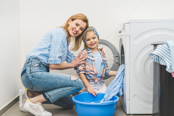 mother and daughter looking at camera while putting clothes into washing machine at home Stock photo © LightFieldStudios