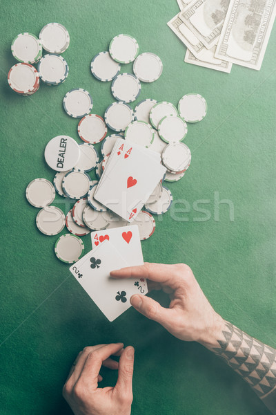 Male hand with poker cards by casino table Stock photo © LightFieldStudios