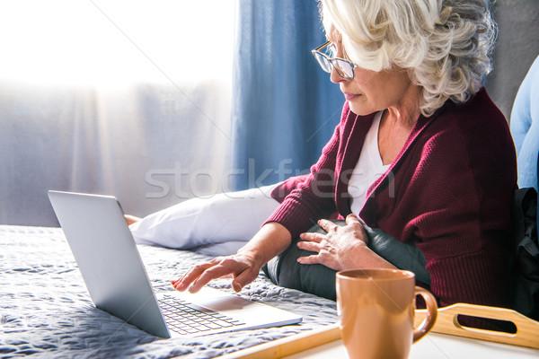 Femme utilisant un ordinateur portable séduisant supérieurs lunettes fond Photo stock © LightFieldStudios