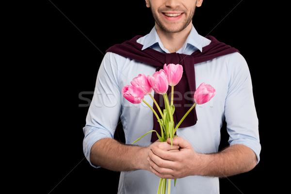 Lövés mosolyog fiatalember tart rózsaszín tulipánok Stock fotó © LightFieldStudios