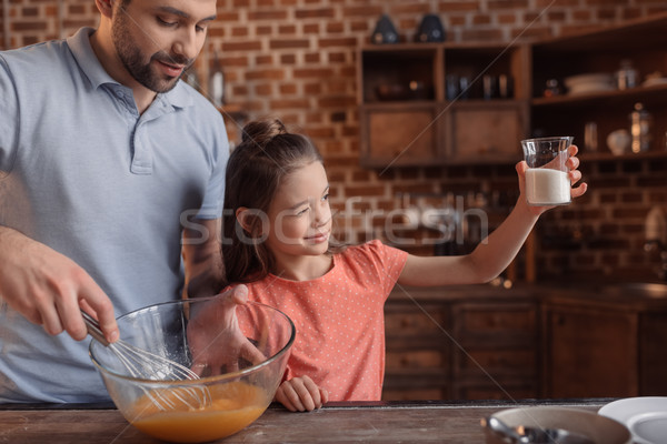 'girl measuring sugar with cooking father near by Stock photo © LightFieldStudios