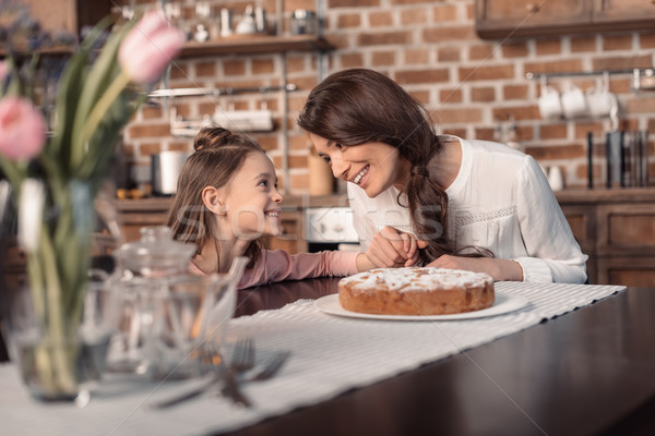 'portrait of cheerful mother and daughter with cake on table, mother's day holiday concept  Stock photo © LightFieldStudios