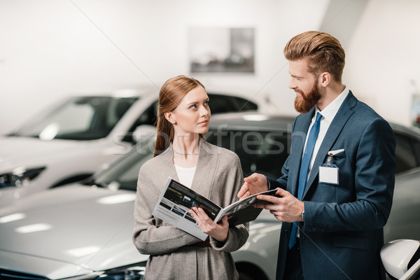 salesman in suit showing catalog to customer in dealership salon   Stock photo © LightFieldStudios
