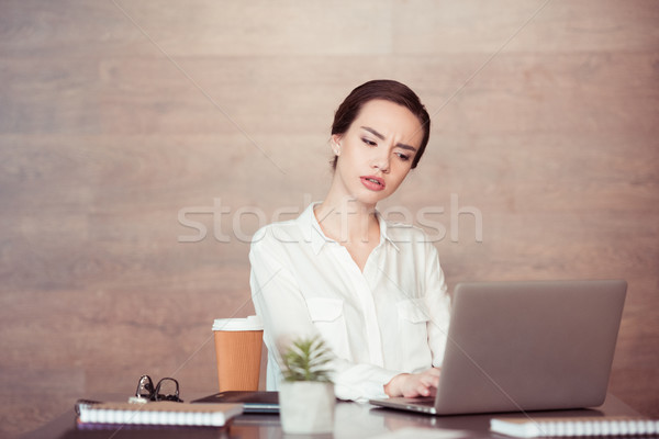 Young overworked businesswoman using laptop at desk Stock photo © LightFieldStudios