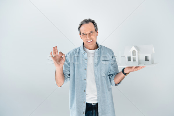 portrait of smiling mature man with house model showing ok sign on grey Stock photo © LightFieldStudios