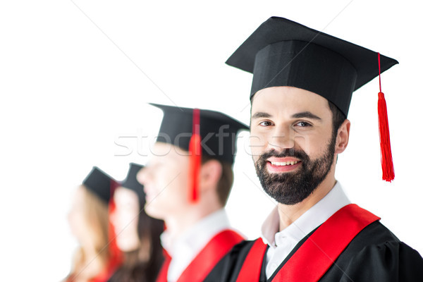bearded student in graduation cap with diploma, with friends behind isolated on white Stock photo © LightFieldStudios