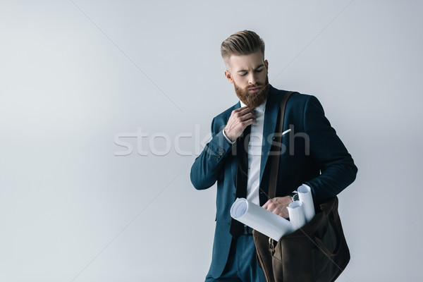 Young bearded businessman with blueprints in shoulder bag adjusting tie Stock photo © LightFieldStudios