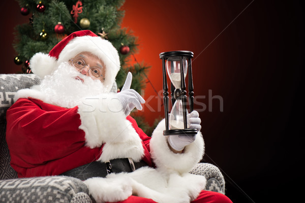 Santa Claus showing hourglass   Stock photo © LightFieldStudios