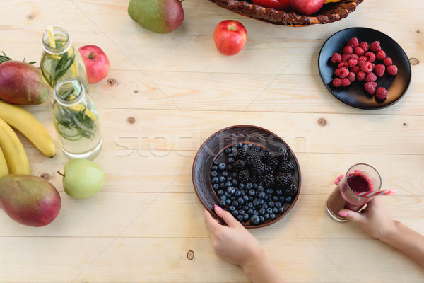 woman with detox drink and berries on plate Stock photo © LightFieldStudios
