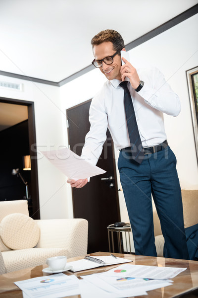 Empresário leitura papelada falante telefone formal Foto stock © LightFieldStudios