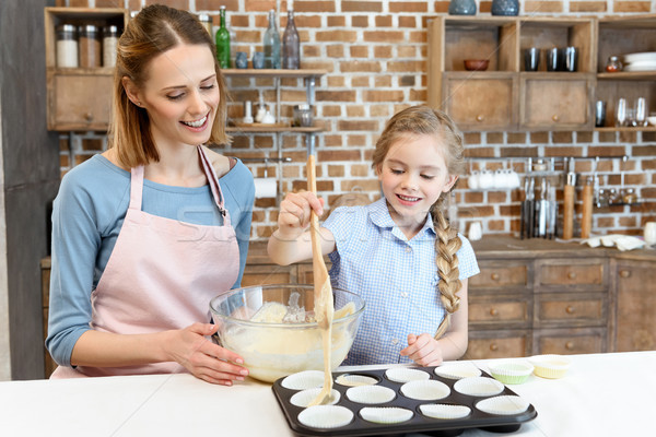 portrait of smiling mother and daughter cooking cupcakes at home Stock photo © LightFieldStudios