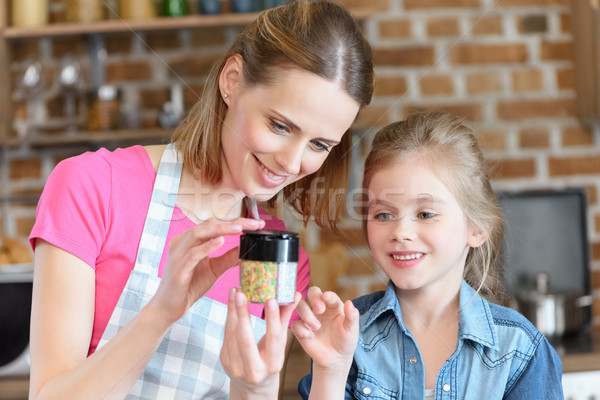 portrait of mother and daughter looking at confetti jar in hands Stock photo © LightFieldStudios