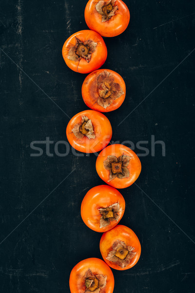 top view of row of persimmons on black Stock photo © LightFieldStudios